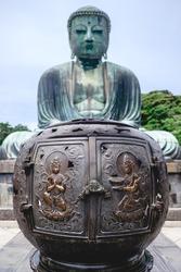 Bronze ornament with carvings and Great Buddha (Daibutsu) bronze statue of Amida Buddha at Kōtoku-in temple, Kamakura, Japan