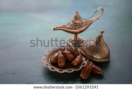 Bronze plate with dates  and aladdin lamp on dark green wooden background. Ramadan background. Ramadan kareem.  #1061293241