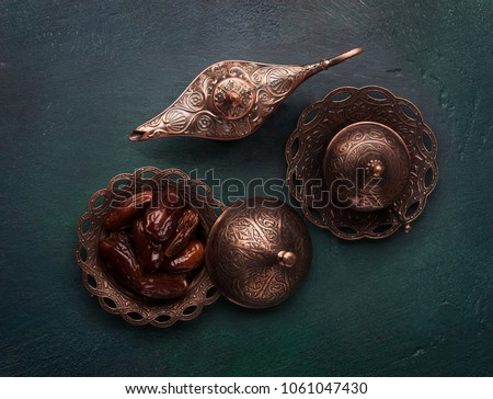 Bronze plate with dates, coffee cup and aladdin lamp on dark green wooden background. Ramadan kareem. Flat lay. #1061047430