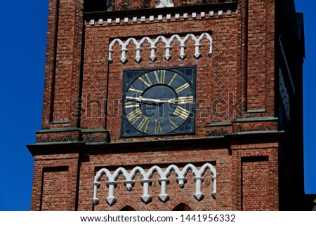 Bronze pointers and numbers of the clock on the church tower #1441956332