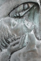 Bronze relief of dead Jesus Christ down from the cross and the Virgin Mary. Easter and religion thematics.