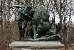 Bronze sculpture of a hunter with a spear rescuing his dog from a bison. Tierpark, Berlin.
