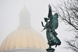 Bronze sculpture of angel with Saint-Isaacs Cathedral golden dome  in background in the mist