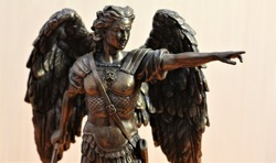 bronze sculpture of Archangel Michael with wings and sword
