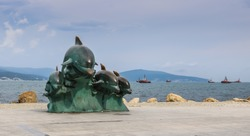Bronze sculpture of dolphins on the background of the Black Sea in Novorossiysk, Krasnodar Territory, Russia.