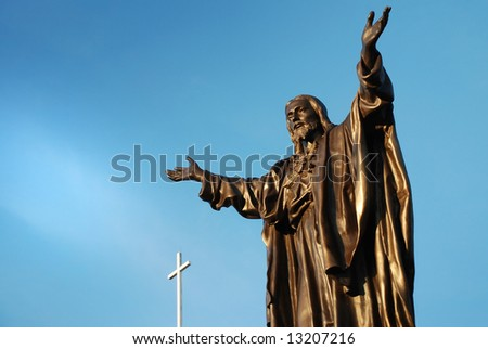 bronze sculpture of Jesus christ  with a white cross