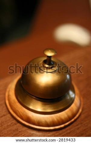 bronze service bell on wooden reception desk