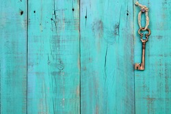 Bronze skeleton house key hanging by rope on blank antique teal blue rustic wood door; real estate background with wooden painted copy space