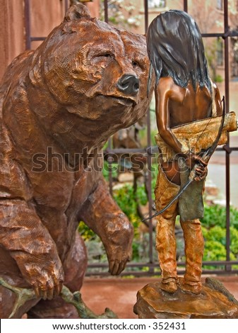 Bronze statue of a bear looking at a young Indian boy at an art gallery in Santa Fe, NM.