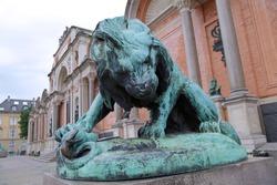 Bronze statue of a lion fighting against a snake in front of Ny Carlsberg Glyptotek in Copenhagen, Denmark