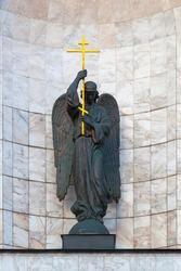 Bronze statue of an angel holding a golden cross.