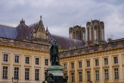 Bronze statue of French King Louis XV on Place Royale (Royal Square) in Reims, France, in front of the classical, 18th century building of the Sub-Prefecture ; behind, the gothic Notre-Dame Cathedral