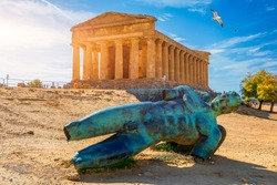 Bronze statue of Icarus in front of the Temple of Concordia at the Valley of the Temples. Temple of Concordia and the statue of Fallen Icarus, in the Valley of the Temples, Agrigento, Sicily, Italy.