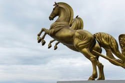 Bronze statue of two horses in motion with sky background and space for text