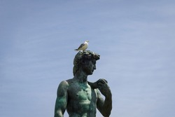 Bronze statue with rust-green tones of Michelangelo's David, with a dove on his head.