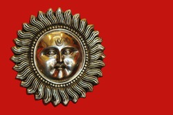 Bronze sun with a face and a mustache on a red background. Surya.