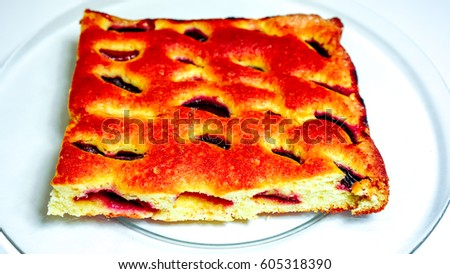 bronze sweet homemade cake with fruit fresh plumps and texture-baked dough cut into square against clear glass plate. Peace of home holiday cake as best addition to a cup of coffee or tea