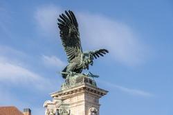 Bronze turul Bird statue on top of column at Sandor Palace on Buda Hill in Budapest winter morning