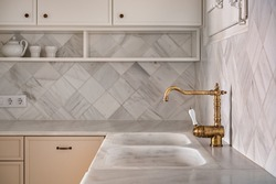 Bronze vintage faucet in empty kitchen interior with light furniture in rustic and retro style with tiled marble walls. Selective focus