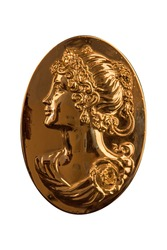 bronze woman's face in a medallion on a black background