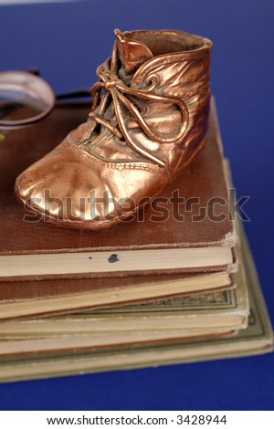 Bronzed baby shoe and old books and glasses.