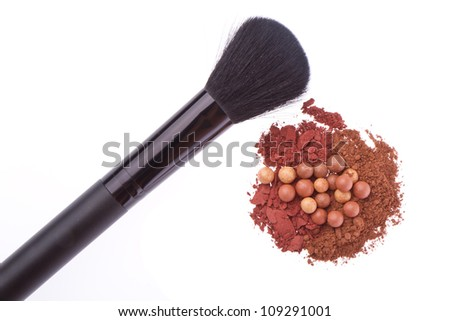 bronzing pearls and crushed eyeshadows with brush isolated on white background