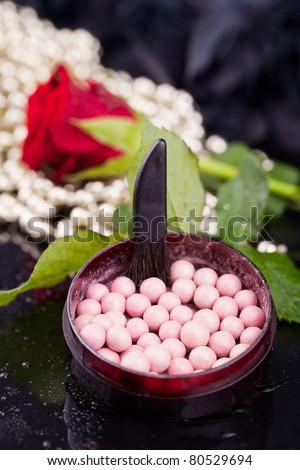 Bronzing pearls in powder box with a brush, on the background of the flowers, pearls, drops of water.