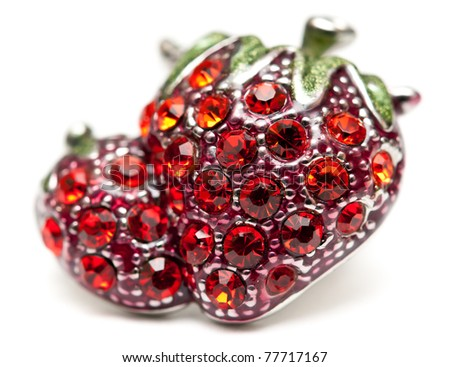 brooch in the shape of strawberries decorated with red jewels on a white background