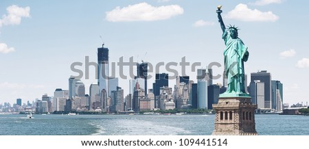 Brooklyn Bridge and Manhattan Skyline with the Statue of Liberty in foreground, New York City.