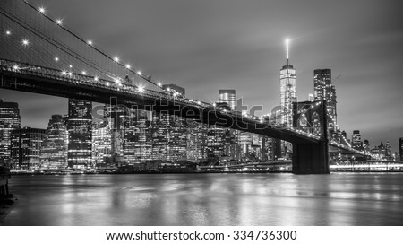 Brooklyn bridge and New York City Manhattan downtown skyline at dusk with skyscrapers illuminated over East River panorama. Copy space. Black and white image. #334736300