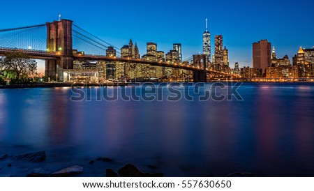 Brooklyn Bridge in the evening with midnight blue sky and smooth water surface shot from Brooklyn side