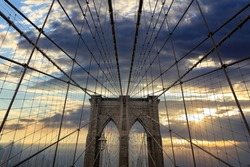 Brooklyn Bridge Manhattan New York USA. Cable bridge tower detail against cloudy sky at sunset background.