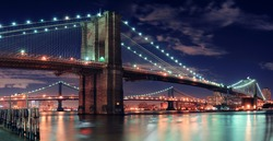 Brooklyn Bridge over East River at night in New York City Manhattan with lights and reflections.