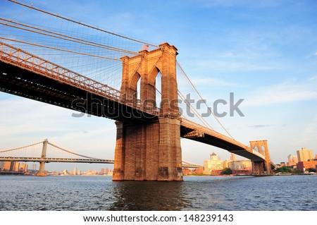 stock photo brooklyn bridge over east river viewed from new york city lower manhattan waterfront at sunset 148239143 - Каталог — Фотообои «Мосты»