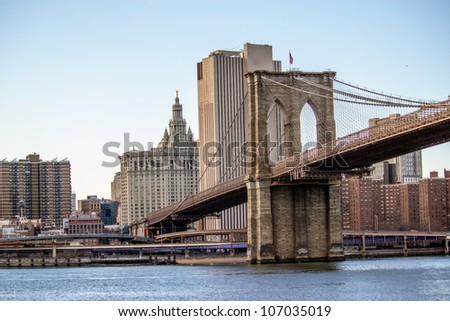 Brooklyn Bridge with  Manhattan skyline panorama in the afternoon with cloud and river reflection over East River in New York City