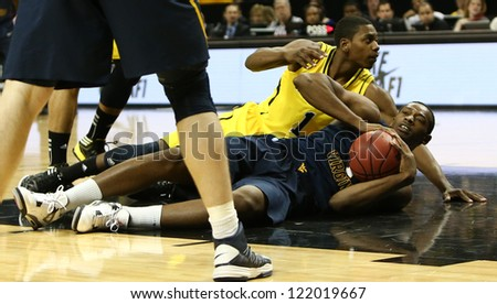 BROOKLYN-DEC 15: Michigan Wolverines forward Glenn Robinson III and West Virginia Mountaineers forward Dominique Rutledge battle for the ball at Barclays Center on December 15, 2012 in Brooklyn.