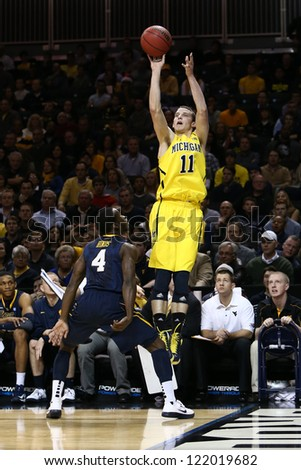 BROOKLYN-DEC 15: Michigan Wolverines guard Nik Stauskas (11) shoots over West Virginia Mountaineers guard Jabarie Hinds (4) during the first half at Barclays Center on December 15, 2012 in Brooklyn.