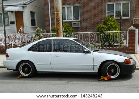 BROOKLYN,NEW YORK - APRIL 30:Two wheel locks on an illegally parked car in Brooklyn, NY on April 30, 2013. NYC started wheel lock program in January 2013.