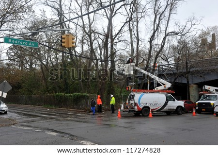 BROOKLYN, NY - OCTOBER 30: A utility company works on overhead wires while the electricity is off  in the Sheapsheadbay neighborhood due to flooding from Hurricane Sandy in Brooklyn, New York, U.S., on Tuesday, October 30, 2012.