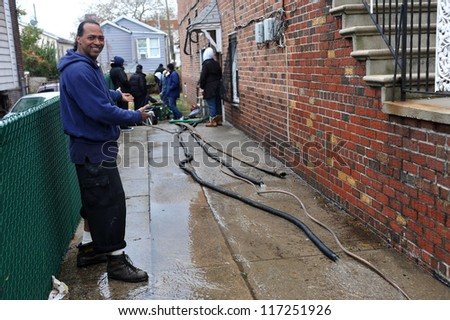 BROOKLYN, NY - OCTOBER 30: People pumping water out of building basement in the Sheapsheadbay neighborhood due to flooding from Hurricane Sandy in Brooklyn, New York, U.S., on October 30, 2012.