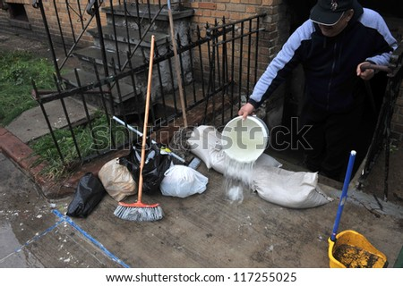 BROOKLYN, NY - OCTOBER 30: Super pumping water out of building basement in the Sheapsheadbay neighborhood due to flooding from Hurricane Sandy in Brooklyn, New York, U.S., on  October 30, 2012. - stock photo