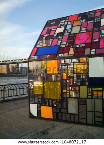 Brooklyn, NY, USA May 25, 2015 A stained glass sculpture, Kolonihavehus by Tom Fruin sits in Brooklyn Bridge Park, overlooking the East River and Manhattan #1048072117