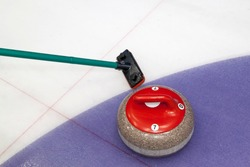 Broom and stone for curling. view of red curling stone in outer blue ring of house with broom nearby