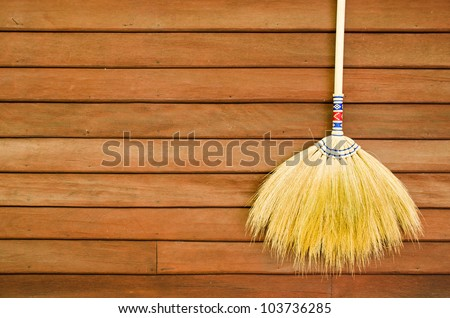 broom hanging on the wooden wall ready for cleaning work