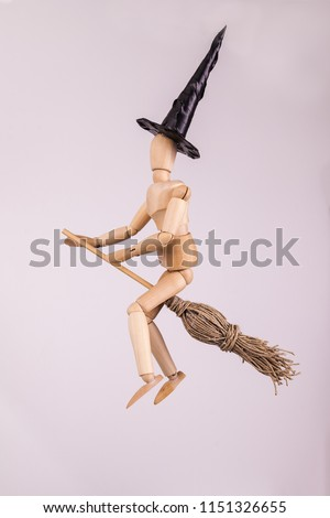 Broom riding halloween witch jointed dummy doll wearing black pointed witches hat on white backdrop #1151326655
