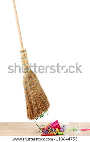 Broom sweep the trash after a party on white background close-up