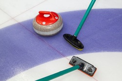 Brooms and stone for curling. view of red curling stone in outer blue ring of house with broom nearby