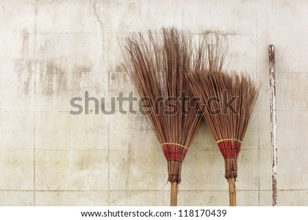 brooms on white wall