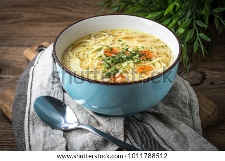 Broth - chicken soup with noodles in a blue bowl.