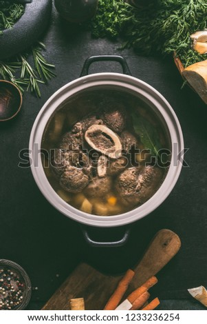 Broth of beef meat shin with bone in cooking pot on dark kitchen table background with ingredients for soup, top view. Meat broth or stock. Clean low-calorie food and eating concept